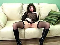 This sassy brunette girl in black lingerie and knee high leather boots knows that she looks hot on the white sofa and never minds performing some erotic poses on cam! voyeur video #3